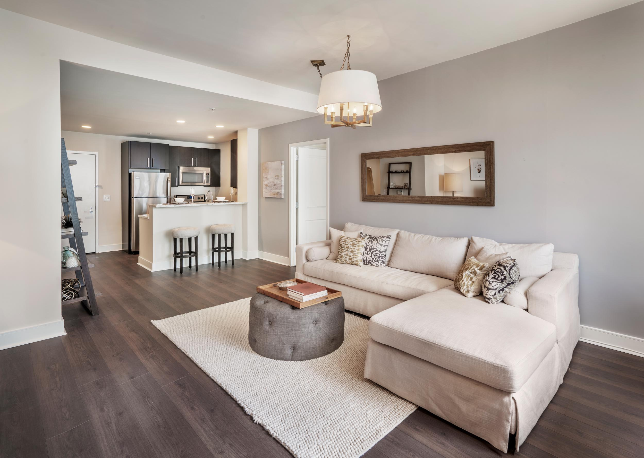 Living room at The Morgan with view into the kitchen including hardwood floors and 9-foot ceiling