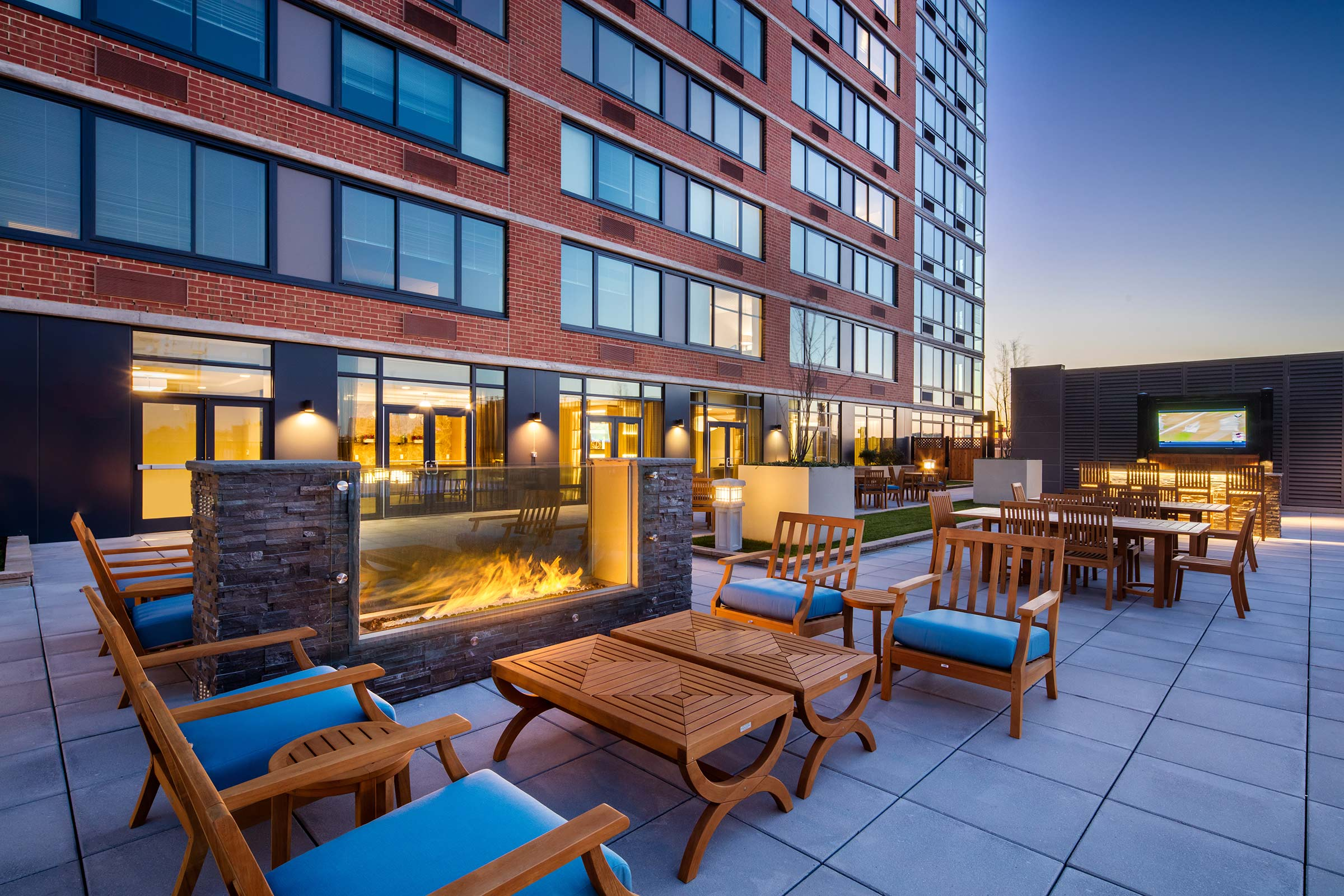 courtyard with fire pit, outdoor seating and wall-mounted TV at The Morgan at Provost Square