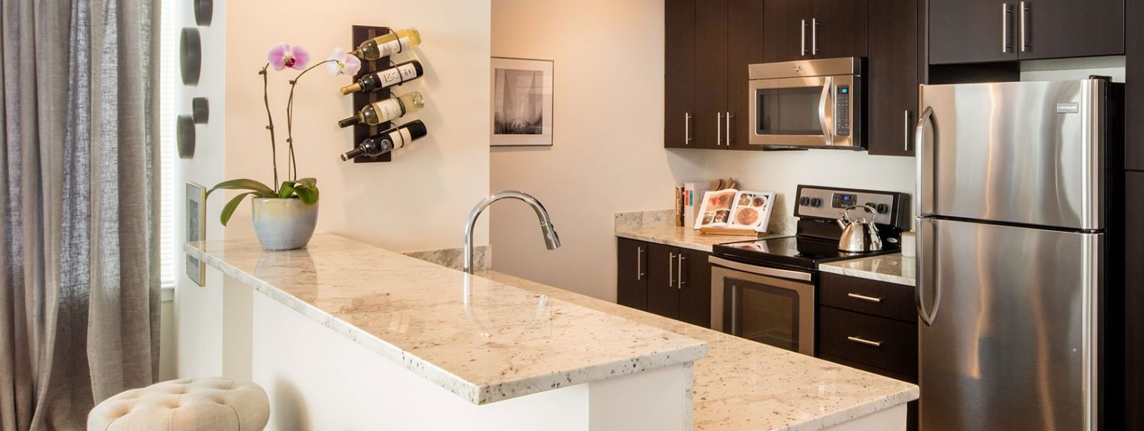 wide angle photo of a kitchen with marble island, brown cabinets and stainless steel appliances at The Morgan at Provost Square apartments